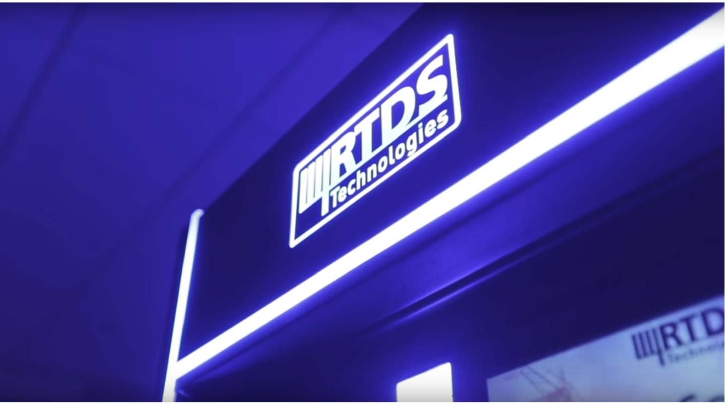 RTDS simulator hardware device is shown in glowing lights.