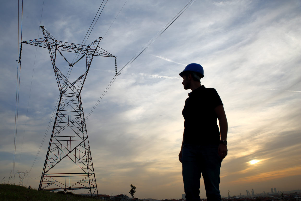 Electrical engineer stands under power lines