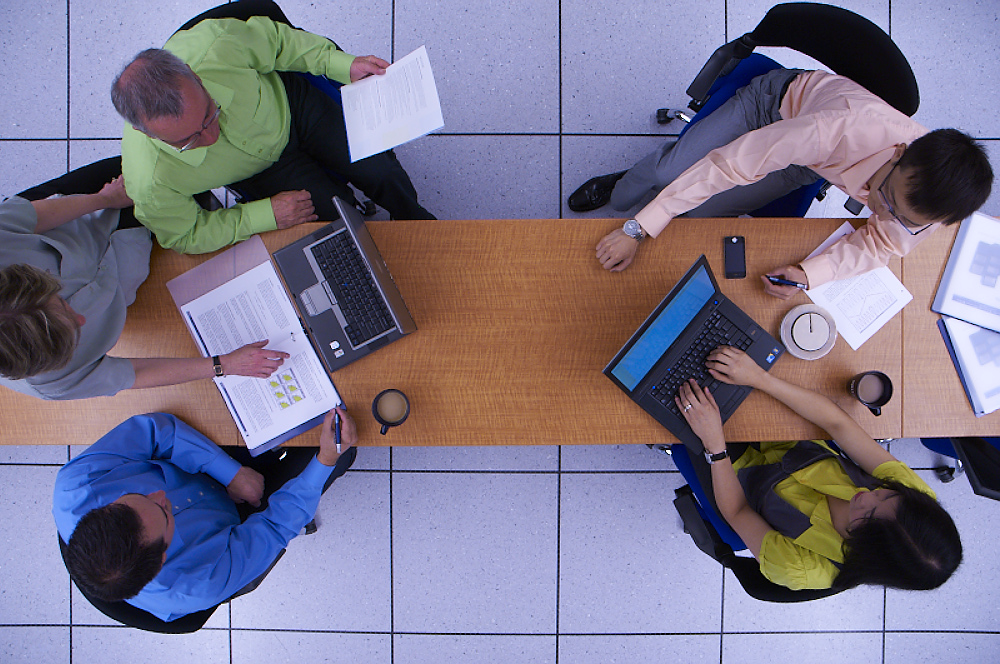 group of people working together around a desk seen from above